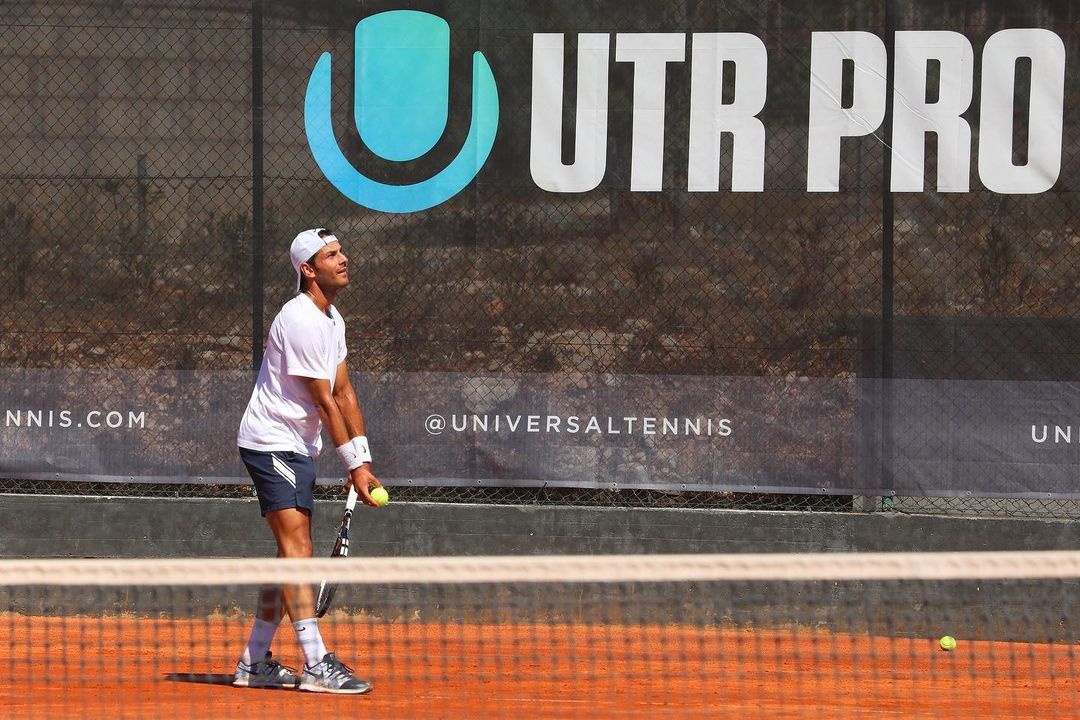 Tennis Player serving in front of UTR Banner